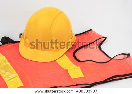 Yellow hard hat and orange and yellow reflective best over white background - stock photo