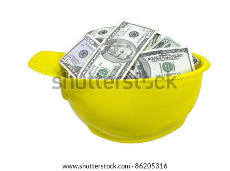 Yellow hard hat worn for protection when working on construction sites full of large amounts of money - path included - stock photo