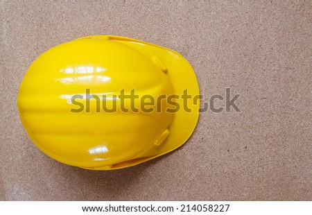 yellow hardhat architect on brown wood background - stock photo