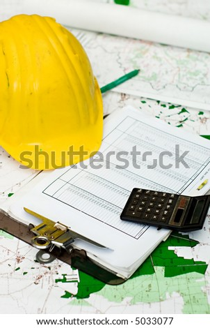 yellow hart hat, clipboard and calculator lying on maps and different plans - stock photo