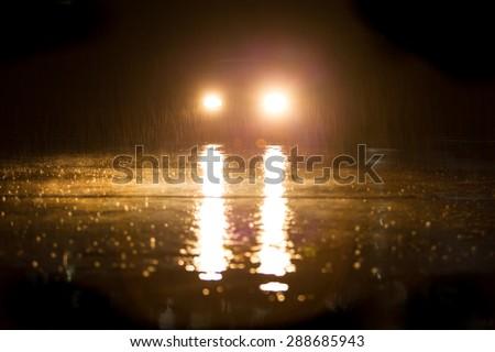 Yellow headlight and road in the dark while heavy raining. - stock photo