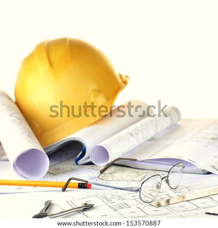 Yellow helmet and heap of project drawings - stock photo