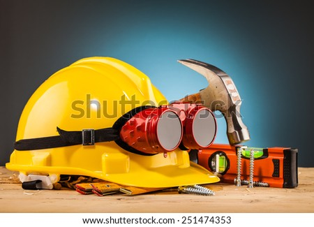 yellow helmet and wood mounting tools on wooden table - stock photo