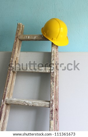 Yellow helmet and wooden step ladder on work place - stock photo