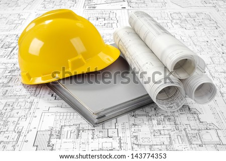 Yellow helmet, grey folder document and project drawings - stock photo