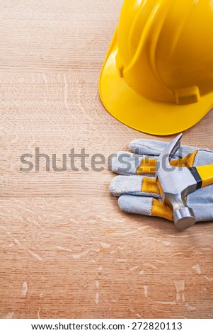 yellow helmet protective glove claw hammer on wooden board construction concept  - stock photo