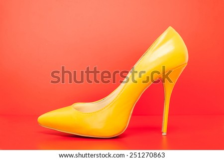 yellow high heels shoes on red background - stock photo