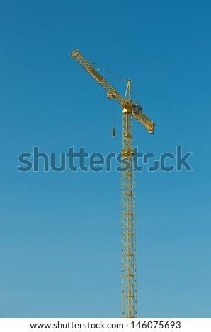 Yellow hoisting crane isolate on blue sky background, the building crane, yellow hoisting crane fragment isolated on blue background, one industrial crane, new technologies in industry  - stock photo