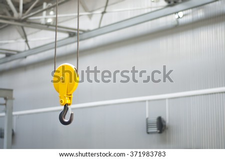 Yellow hook of the crane working at a warehouse - stock photo