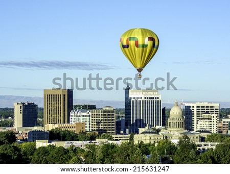 Yellow hot air ballon over the IDaho capital - stock photo