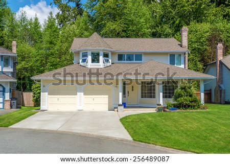 Yellow house with beautiful landscaping. Home exterior. - stock photo