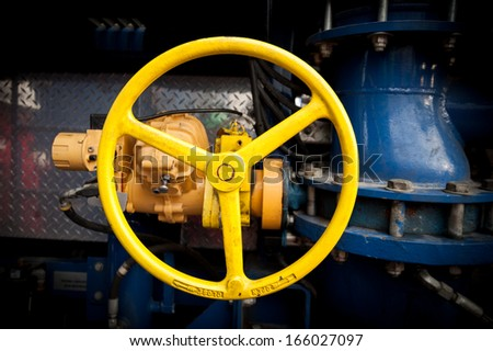 Yellow industrial valve in a large system - stock photo