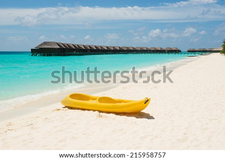 Yellow kayak on the tropical beach, with water villa in background - stock photo