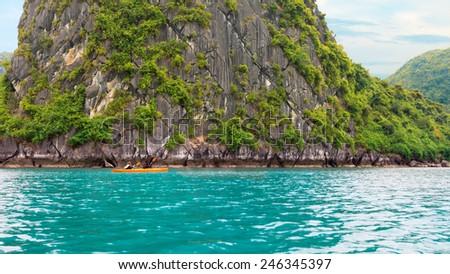 Yellow kayak on turquoise sea water and rock background - stock photo