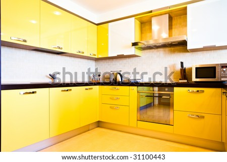 Yellow kitchen interior in modern flat - stock photo