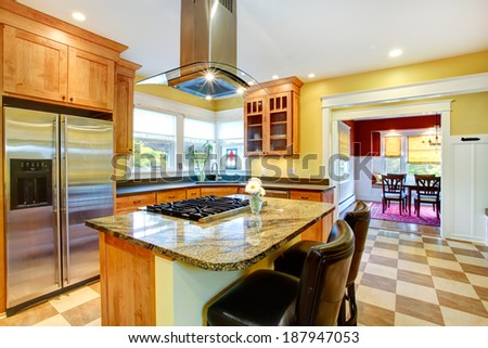 Yellow kitchen interior. View of island with built-in stove and kitchen hood above it. - stock photo