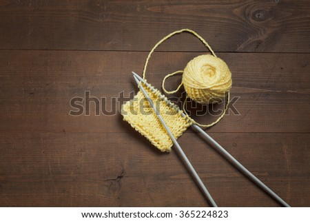 yellow knitting wool and knitting needles on wooden background table - stock photo