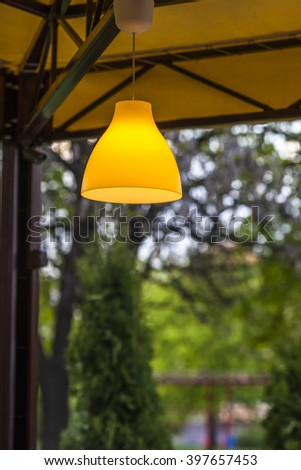 Yellow lamp hanging outside against green forest background - stock photo