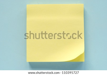 Yellow leaf of a reminder on a blue background - stock photo