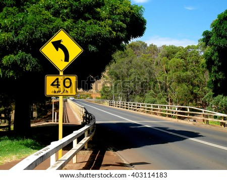 Yellow left curve ahead sign and speed limit sign - stock photo