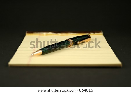 Yellow legal pad and pen - stock photo