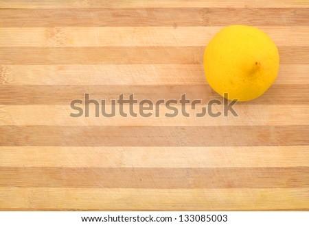 Yellow lemon  sit on a worn butcher block cutting board - stock photo