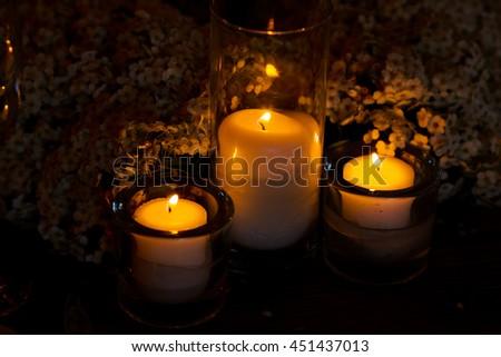 Yellow light from the candles illuminates tiny flowers - stock photo