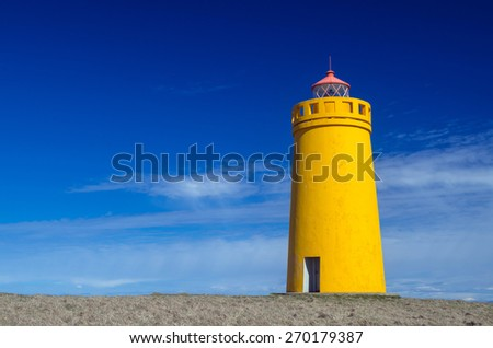 Yellow lighthouse and clear blue sky - stock photo