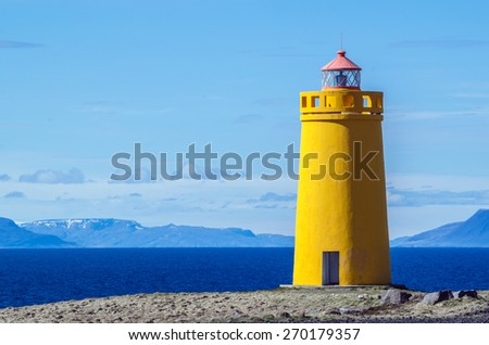 Yellow lighthouse and on a clear and sunny day - stock photo