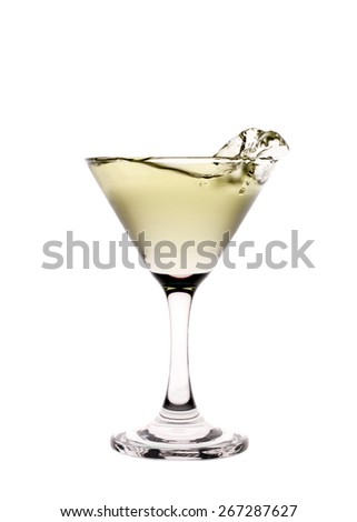 Yellow liquid splashing in a martini glass isolated on white background - stock photo