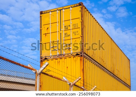 Yellow metal industrial cargo containers are stacked under blue cloudy sky - stock photo
