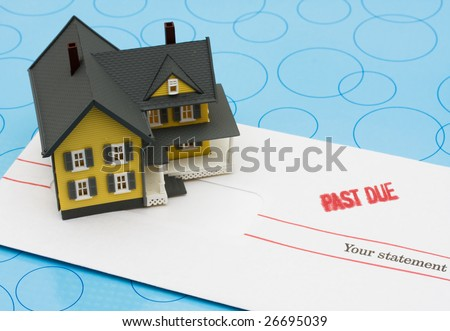 Yellow model house with past due bills sitting on a blue background, yellow house - stock photo