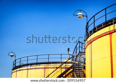 yellow modern storage tanks in front of blue sky - stock photo