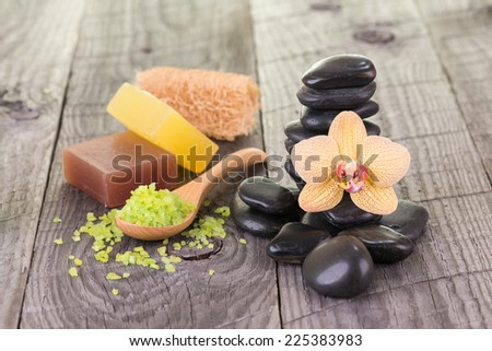 Yellow Moth orchid, bath salt, soaps and loofah on weathered deck close up - stock photo