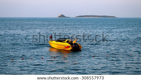 yellow motor boat on the sea on the backdrop of the island   - stock photo