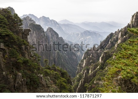 Yellow mountain valley in China during daylight with mountain range and sky in background - stock photo