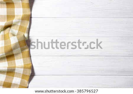 Yellow napkin on the old wooden table. - stock photo