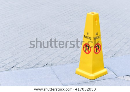yellow no parking cone on the street - stock photo