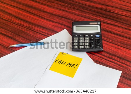Yellow note with the words Call me written on it. The note is attached to a sheet of paper with a heart shaped paper clip - stock photo
