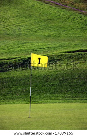 Yellow number one flag marking the first hole on a golf course - stock photo