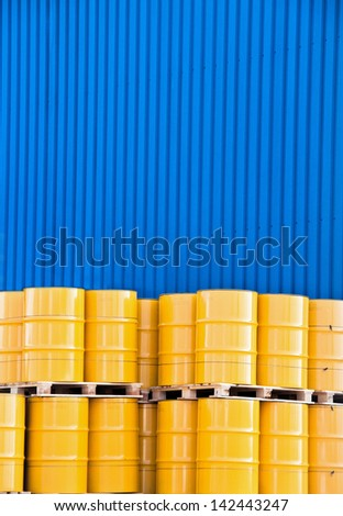 Yellow oil drums and a blue factory cladding - stock photo