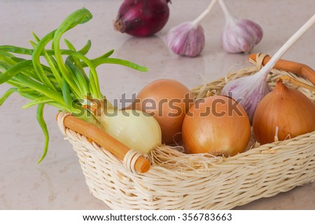 Yellow onions and green onions with regrown roots, garlic in a straw basket. In the background, two heads of garlic and red onion - stock photo