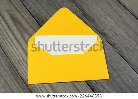 yellow open enveloped with blank card on wooden background  - stock photo