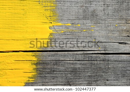yellow paint on old wooden background - stock photo