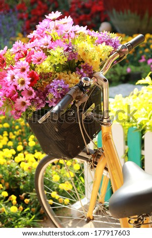 Yellow painted bicycle with a bucket of colorful flowers - stock photo