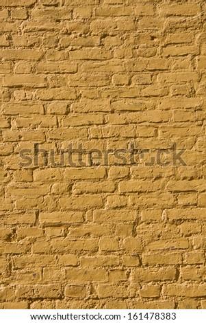 Yellow painted weathered brick wall background. Close up - stock photo
