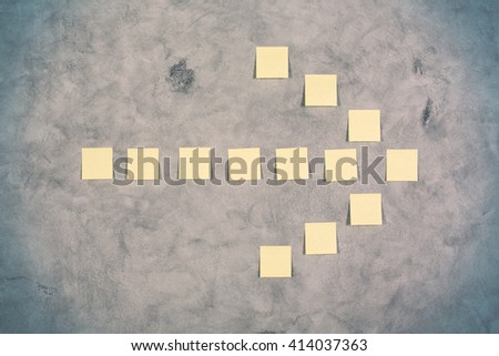 Yellow paper sticker arrow on concrete wall - stock photo