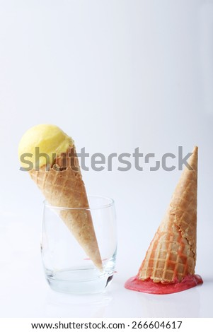 yellow passion fruit ice cream cone in glass and red strawberry ice cream cone dropped melt on ground - stock photo