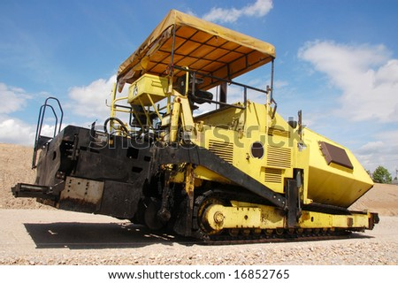 Yellow paver machine for road construction - stock photo