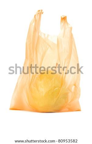 Yellow pear in orange plastic bag on white background - stock photo